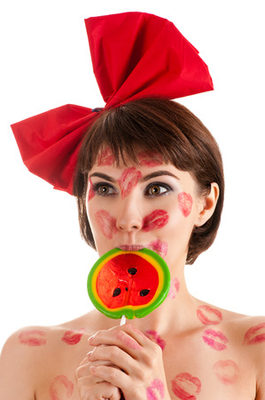 kissing lips: pretty girl with a red bow and lollipop in mouth in lipstick kisses Stock Photo