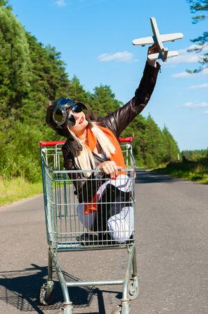 lady fly: woman in aviator helmet on the trolley with toy airplane outdoors