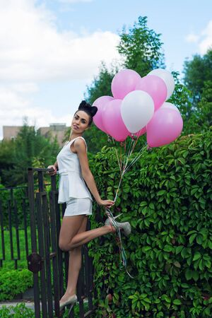 puertas de hierro: mujer atractiva con globos en las puertas de hierro Foto de archivo