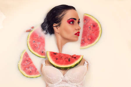 top model: beautiful woman lying in milk with slices of watermelon Stock Photo