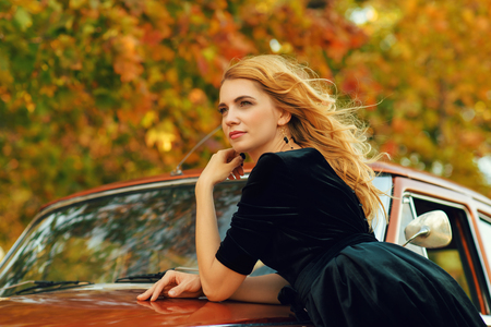 beautiful blond woman with a retro car in autumn