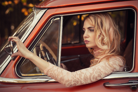 attractive woman looking at the side mirror retro car