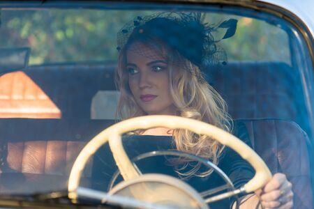 beautiful blonde woman: fashionable woman at the wheel of a retro car Stock Photo