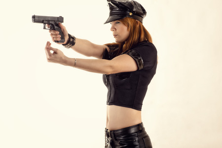 disarm: woman police officer aiming a pistol and hand gestures Stock Photo