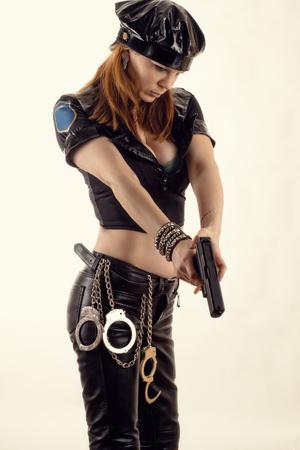 bdsm handcuff: beautiful police woman aiming a pistol Stock Photo