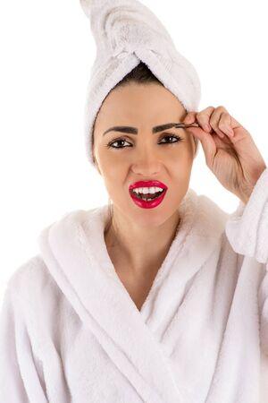 painfully: beautiful woman in bathrobe plucks eyebrows Stock Photo