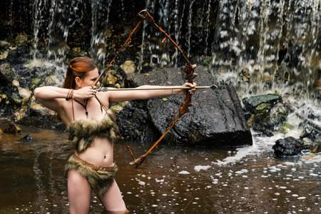 woman archer shoots bow on background waterfall