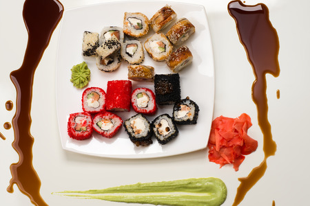 japanese cookery: assorted rolls, ginger, wasabi and soy sauce on white background Stock Photo
