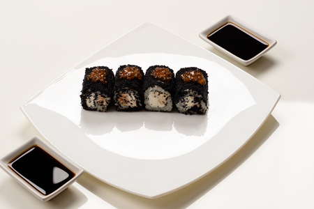 saucers: rolls with black caviar on a white plate with saucers