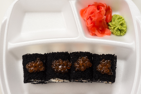 japanese cookery: delicious rolls with black caviar on plate from above