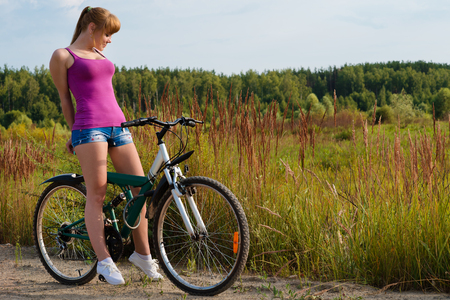 elegant woman on bicycle outdoors