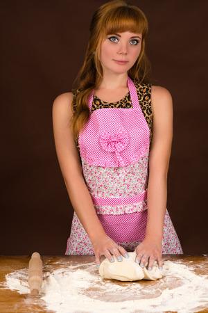 preparing dough: woman in apron preparing dough on table Stock Photo