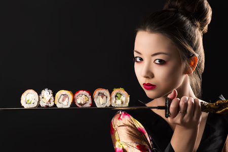 beautiful girl samurai with sword and rolls Stock Photo