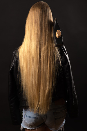 blond teenager girl with long hair and ax Stock Photo