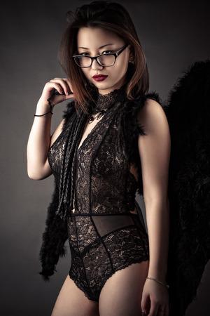Luxe vrouw met zweep in handen met zwarte vleugels