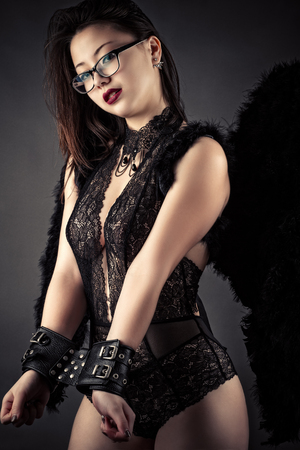 luxurious beautiful woman in handcuffs and black wings Stock Photo