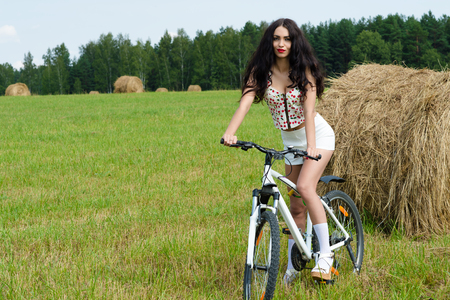 beautiful brunette woman on bicycle in the field