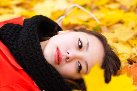 attractive Korean girl with glasses lying on leaves