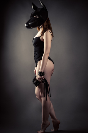 Beautiful woman in dog mask with whip in hands