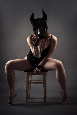 Sexy woman in dog mask and leash shows a gesture with finger Stock Photo