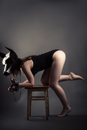 Seduction woman in dog mask and leash shows a gesture finger Stock Photo