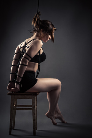 Beautiful female slave sitting bondage ropes on chair