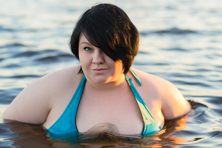 attractive fat woman swimming in water