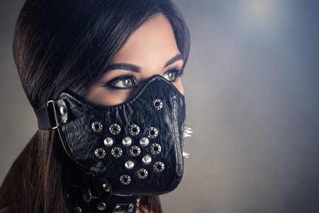 beautiful portrait of woman slave in mask with spikes