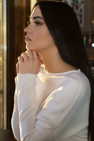 pretty pensive woman wearing a white sweater