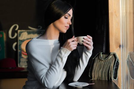 elegant brunette with cup of coffee