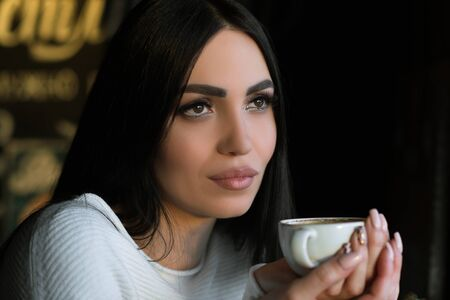 attractive brunette woman having cup of coffee