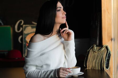 attractive brunette woman with cup of coffee looking pensive