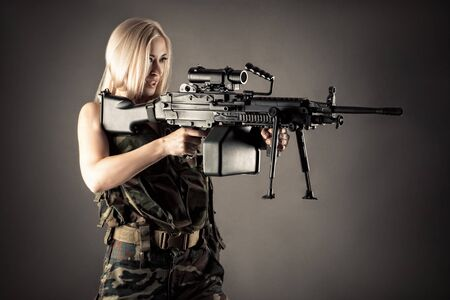 beautiful woman blonde aiming machine gun Zdjęcie Seryjne