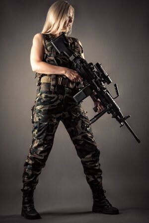 luxurious blonde in uniform with machine gun in hands