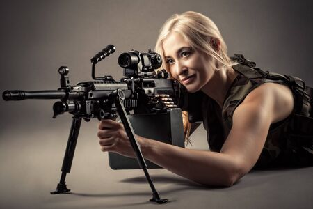 beautiful blond woman aiming machine gun while lying on the floor