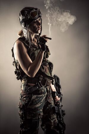 woman in uniform with guns rests smoking cigar