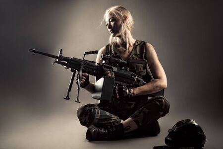 attractive blond woman with machine gun in hands