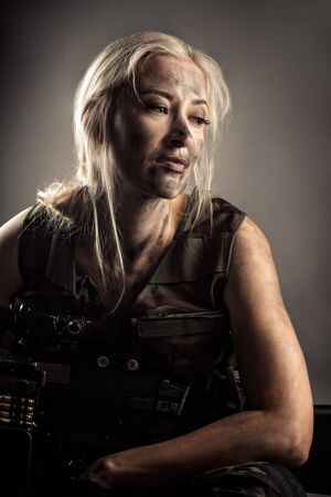 portrait pensive woman with machine gun in hands