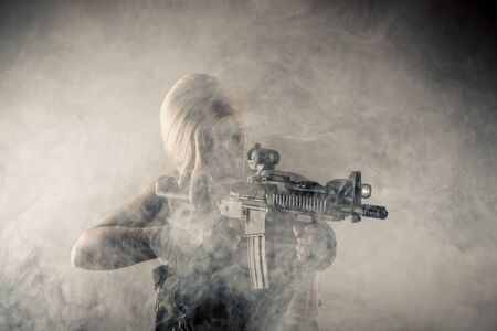 brutal woman with gun in hands in smoke
