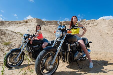 two young girls on motorcycles in summer