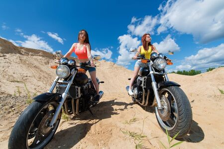 two attractive women on motorcycles outdoors