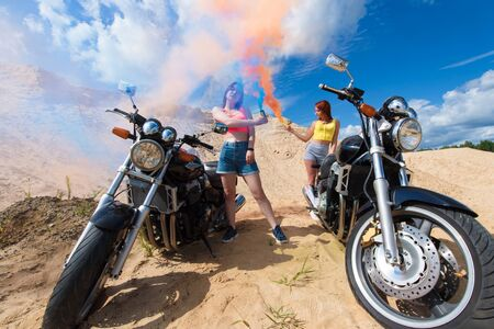 two attractive young girls on motorbikes with smoke bombs