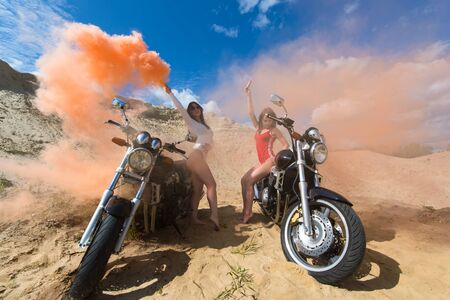 two beautiful young girls on motorbikes with smoke bombs Zdjęcie Seryjne