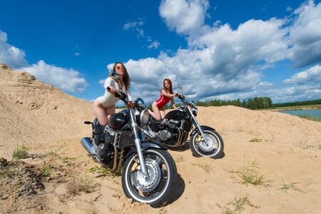 two sensual woman in swimsuits relaxing on motorbikes