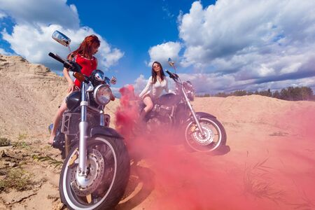 two sensual woman on motorbikes with red smoke