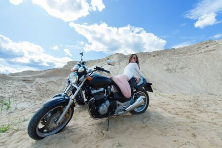 attractive sensual woman lies on motorcycle among the sands