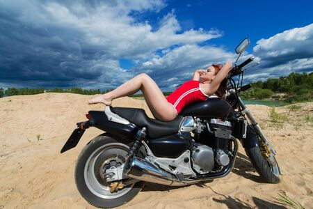 beautiful sensual woman lying on motorcycle