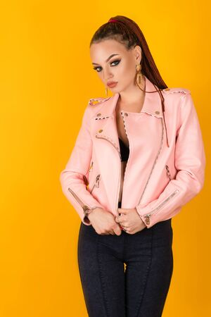 beautiful woman in pink jacket on yellow background Zdjęcie Seryjne