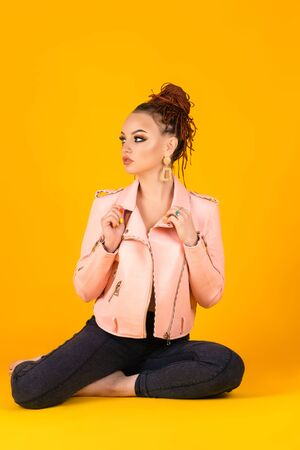 fashionable woman in pink jacket sitting on yellow background