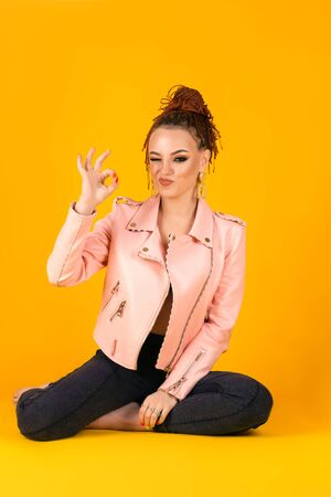 stylish young woman in pink jacket shows ok gesture